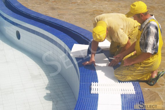 Photos of works on laying tiles for the pool and drain mechanisms