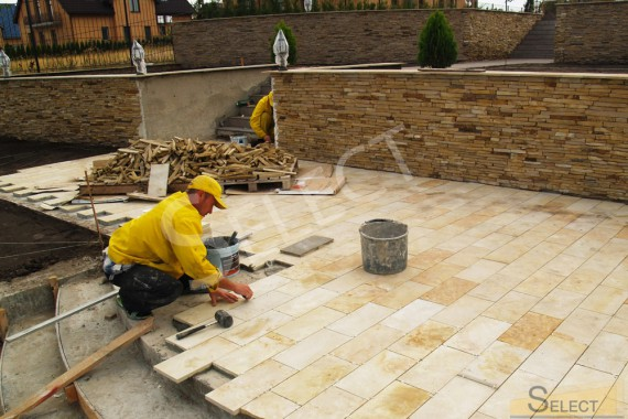 Laying paving slabs on a suburban area porcelain stoneware, sandstone