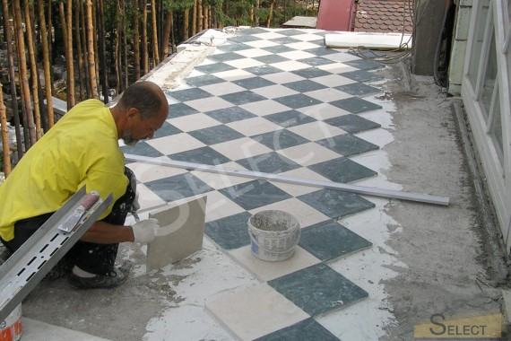 Laying the floor with marble street tiles in a checkerboard pattern