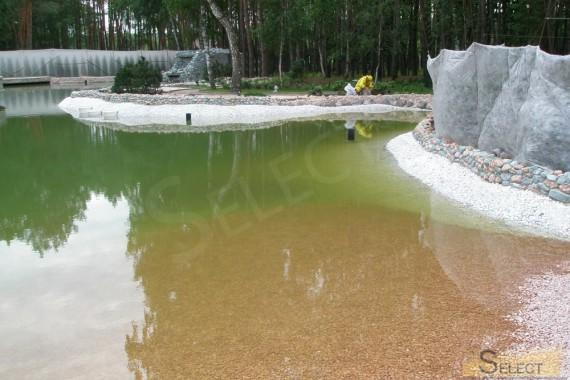 Наполнение водой искусственного пруда на заднем дворе виллы