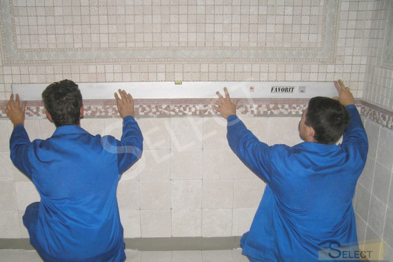 Photo Workers check the level of tile laying